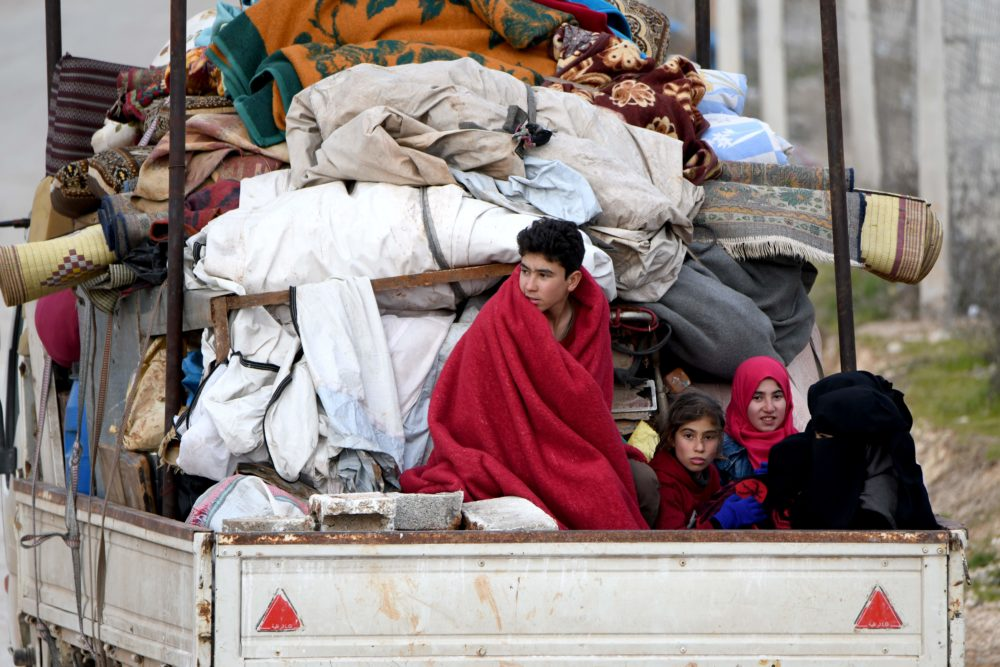 People ride in the back of a truck with furniture, mattresses, and blankets while passing by an internally-displaced persons (IDP) camp near the Turkish border in the west of Syria's northern province of Aleppo on Feb. 16, 2020, fleeing advancing Syrian government forces in Idlib and Aleppo provinces. (Rami al Sayed/AFP/Getty Images)