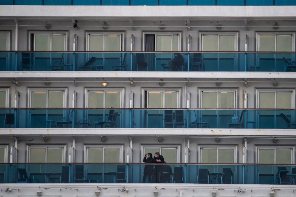 Passengers wearing face masks look out from their cabin on the Diamond Princess cruise ship in quarantine due to fears of COVID-19. (Philip Fong/AFP/Getty Images)