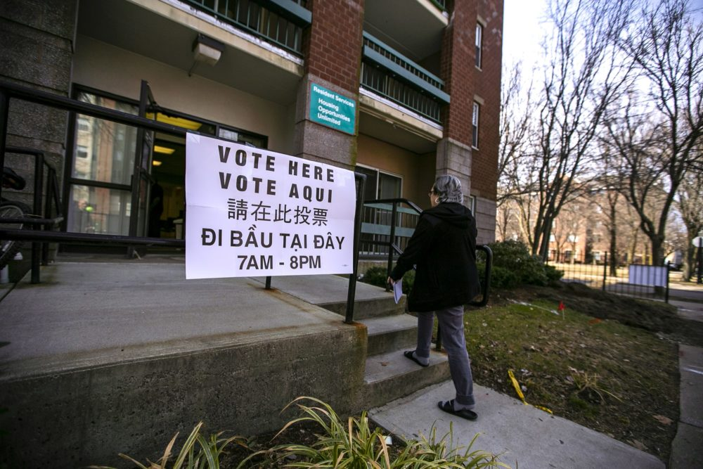 A resident of Harbor Point Apartments in Dorchester climbs the steps to the polling location to vote. (Jesse Costa/WBUR)