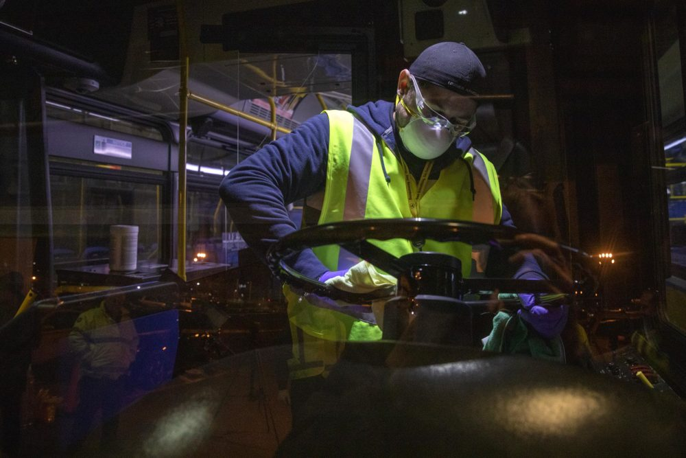 The MBTA's Fradwin Suarez wipes down the steering wheel of the bus overnight at the Charlestown bus garage. (Robin Lubbock/WBUR)