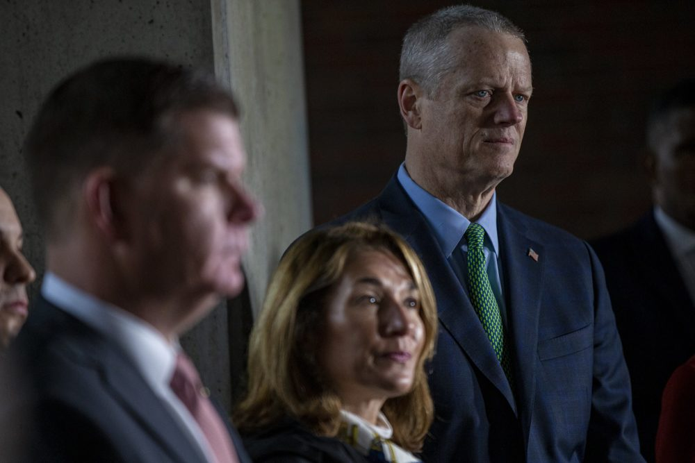 Gov. Charlie Baker (right), looks on at a press conference on City Hall Plaza, along with Boston Mayor Marty Walsh and Lt. Gov. Karyn Polito. (Jesse Costa/WBUR)