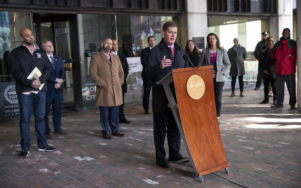 Boston Mayor Marty Walsh, flanked by city councilors and staff, at a press conference in front of City Hall. (Robin Lubbock/WBUR)