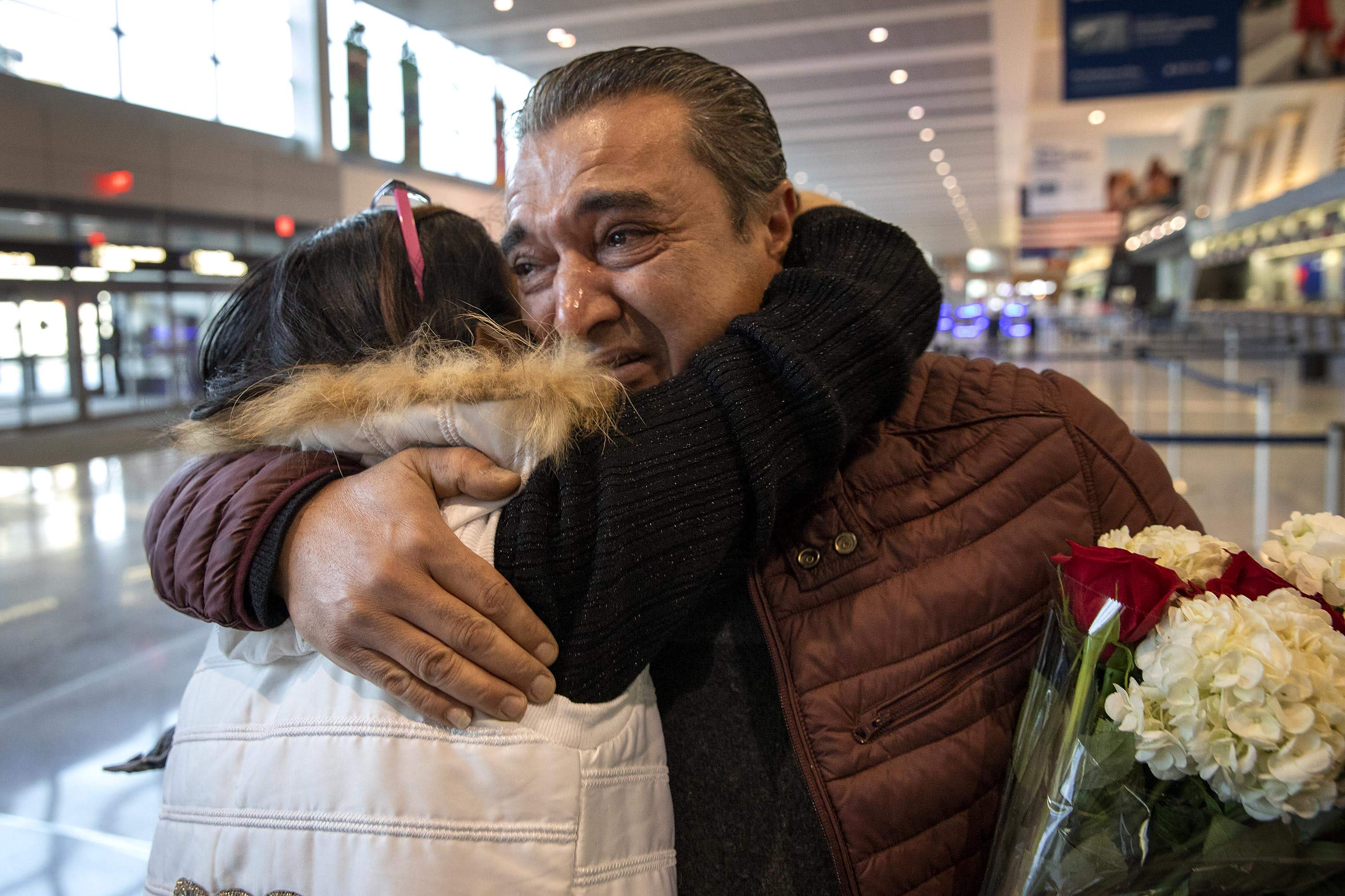 Alaa Issa hugs his sister Lina, as she and her family arrive at Logan Airport. (Robin Lubbock/WBUR)