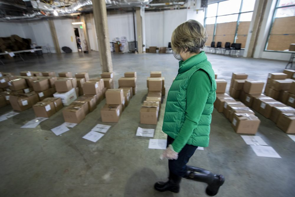 A worker examines boxed-up course material for each Boston Public Schools student to resume their coursework remotely with the Chomebook they will receive. (Jesse Costa/WBUR)