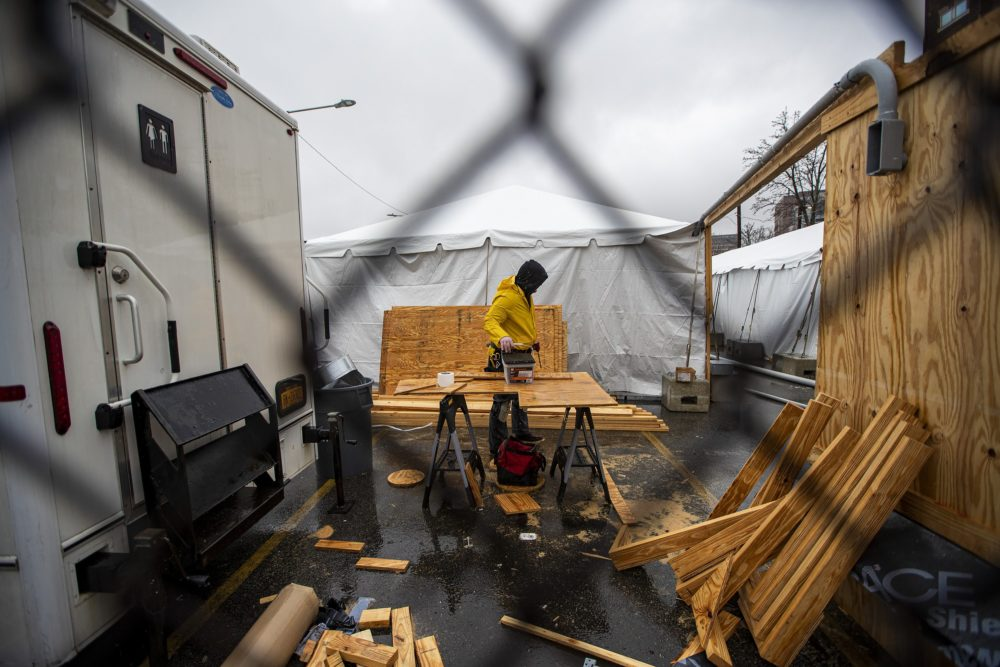 A contractor picks up a box of screws from a work bench during construction of tents for people who are homeless and affected by the coronavirus behind the Southampton Street shelter in Boston. (Jesse Costa/WBUR)