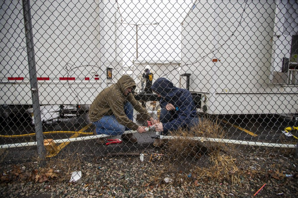 Two contractors work on plumbing for water distribution during construction of Coronavirus testing tent for homeless behind the shelter on Southampton St. in Boston. (Jesse Costa/WBUR)