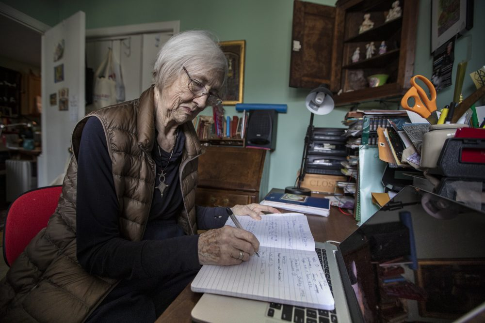 Jane Poncia writes in a notebook in her office at her home in East Boston. (Jesse Costa/WBUR)