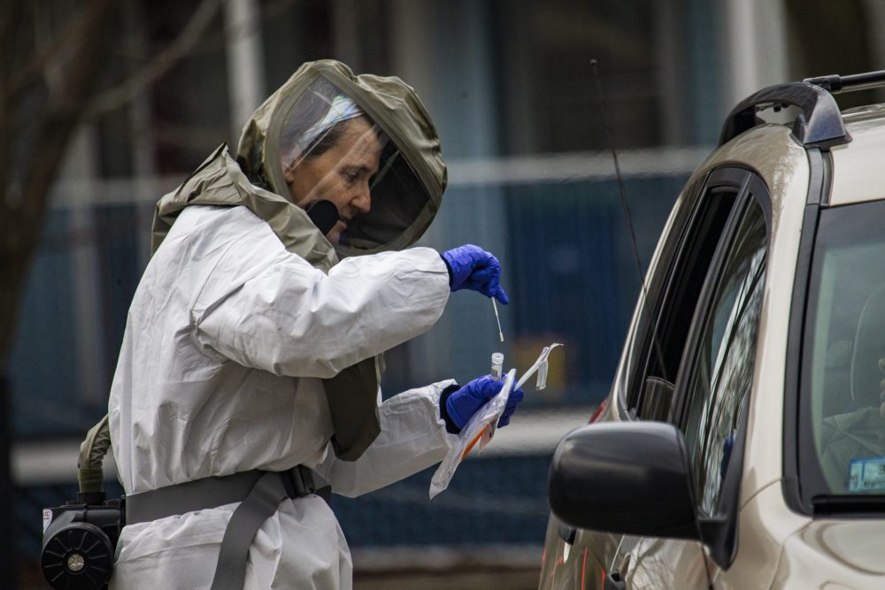 A health care worker in a haz-mat suit places a cotton swab into a vial after taking the sample from someone being tested for COVID-19 at a drive-thru testing area at Somerville Hospital. (Jesse Costa/WBUR)