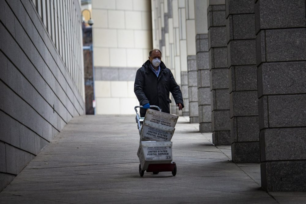A mail carrier wityh a mask walks through the Edward Brooke Courthouse Plaza. (Jesse Costa/WBUR)