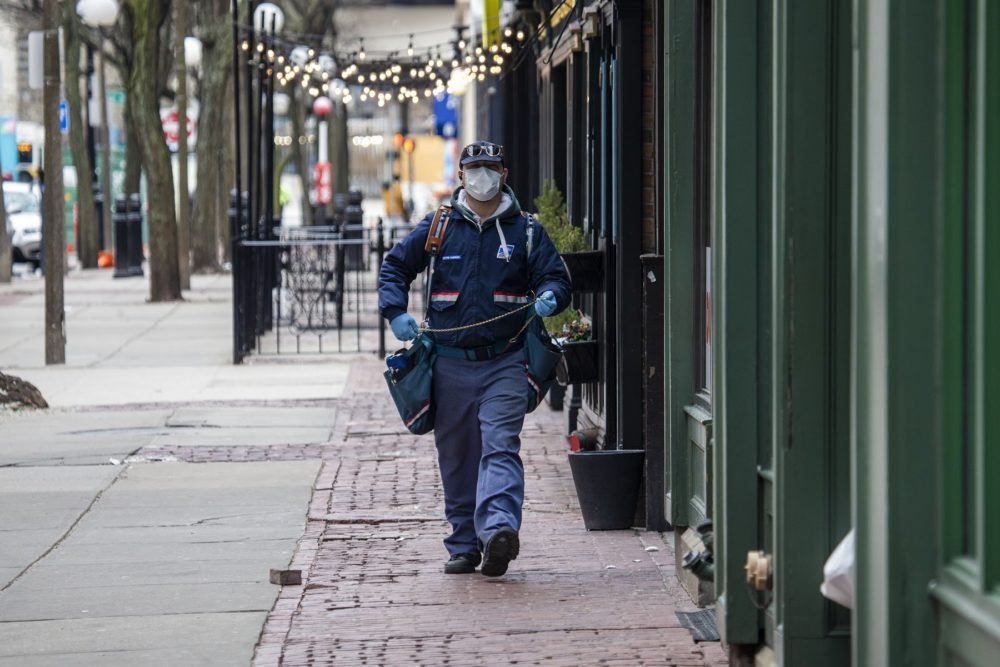 A U.S. postal mail carrier with a mask delivers mail on Canal Street by North Station. (Jesse Costa/WBUR)