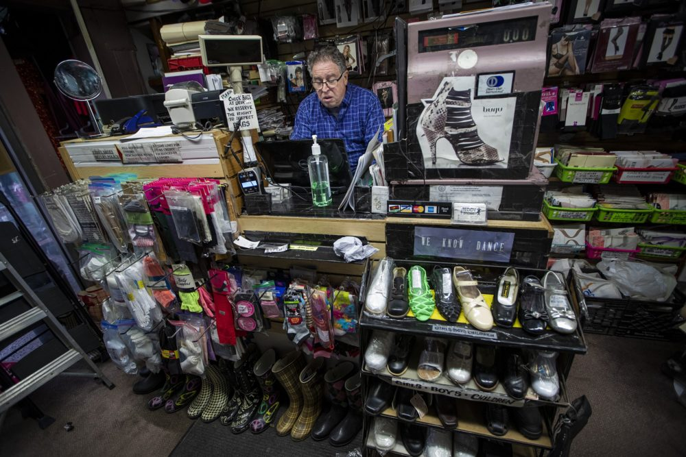 Teddy Shoes owner Steven Adelson sits behind the counter of his store working on a GoFundMe page. He hopes with the combination of online sales and donations he receives, he will be able to keep his business. (Jesse Costa/WBUR)