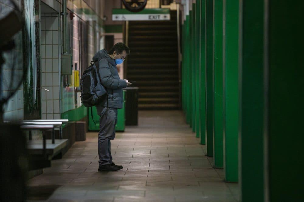 A man waits for a train in the Arlington MBTA station. (Jesse Costa/WBUR)