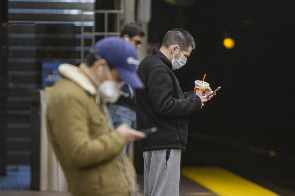 Two passengers wearing masks waiting for a Green Line train at the MBTA station at Park Street. (Jesse Costa/WBUR)