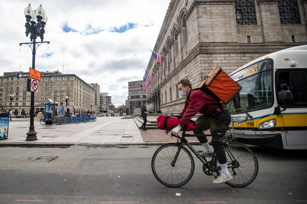 A food delivery bike courier rides down Boylston Street during the lunch hour. (Jesse Costa/WBUR)