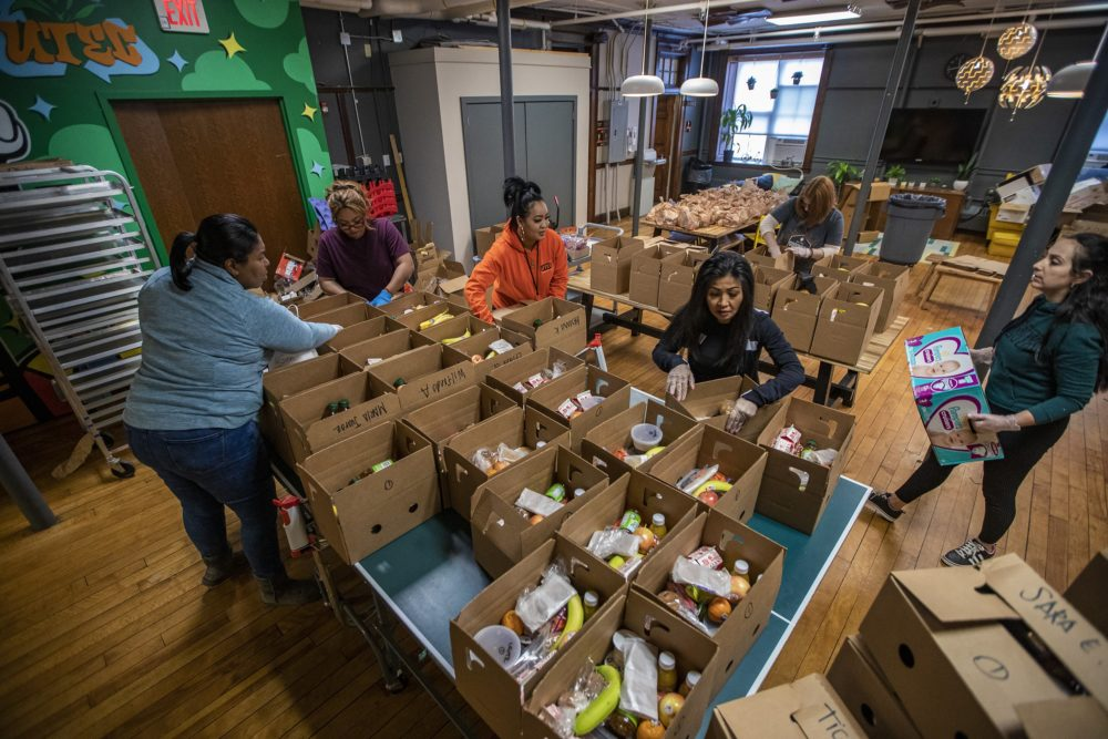Workers at UTEC assemble meal boxes for their young people at home since the program is shut down. (Jesse Costa/WBUR)
