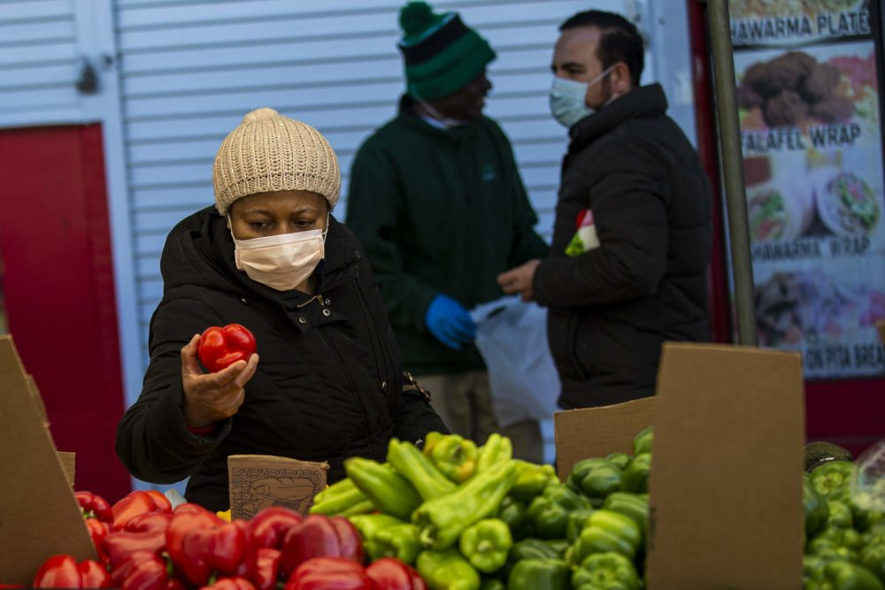 A woman picks up and inspects a pepper at Haymarket on Blackstone Street. (Jesse Costa/WBUR)