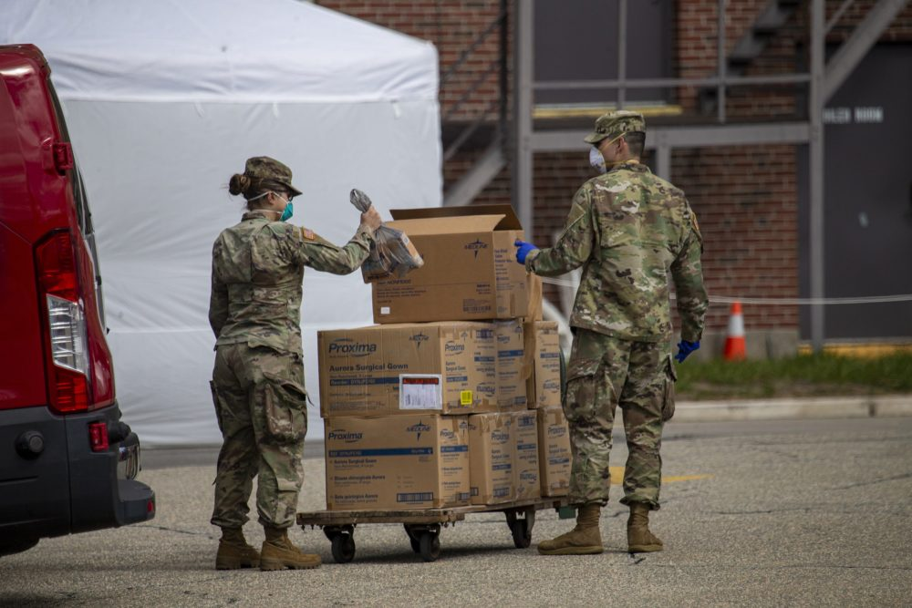 Members of the National Guard load boxes of protective gear onto a cart at the Soldiers' Home — a state-run long-term residence and health facility in Holyoke where 11 veterans have died following a coronavirus outbreak — on March 31. (Jesse Costa/WBUR)