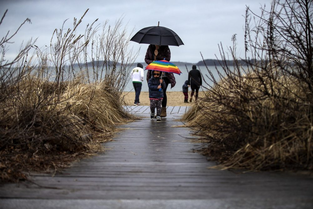 Two-year-old Jonah Klein and his mother Stephanie return from a quick morning walk in the cold rain along Carson Beach in South Boston. (Jesse Costa/WBUR)