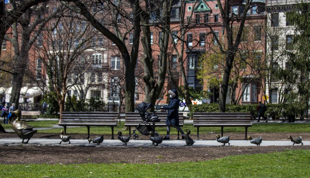 A woman wheels a carriage past the Make Way For Ducklings sculpture in the Boston Public Garden. (Jesse Costa/WBUR)