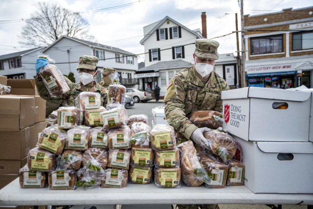 U.S. Army National Guard place loaves of bread for residents of Chelsea to pick up during a pop-up food pantry at Washington Park. (Jesse Costa/WBUR)
