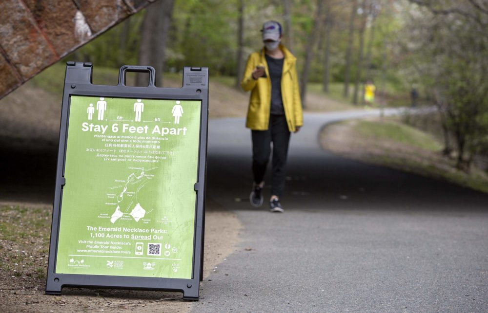 A sign urging social distancing in Brookline on the Emerald Necklace pathway. (Robin Lubbock/WBUR)