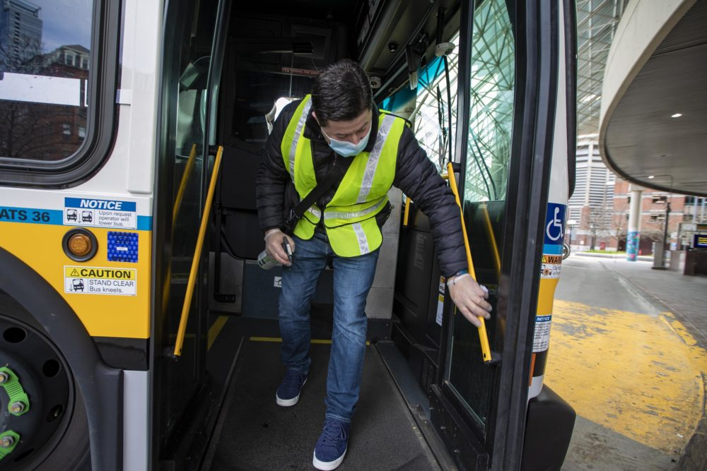 Diego Zabata finishes up disinfecting an MBTA bus at Haymarket Station after it finished its route from Woodlawn in Everett. (Jesse Costa/WBUR)
