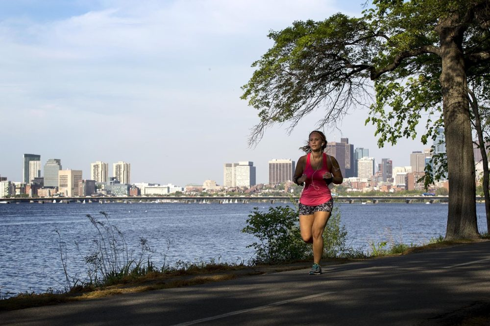A woman runs along the Charles River in Boston. (Robin Lubbock/WBUR)