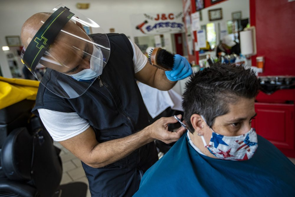 Leuris Luna gives a haircut to a customer at J&C Barber Shop in Roxbury, the first day of reopening during the COVID-19 pandemic. (Jesse Costa/WBUR)
