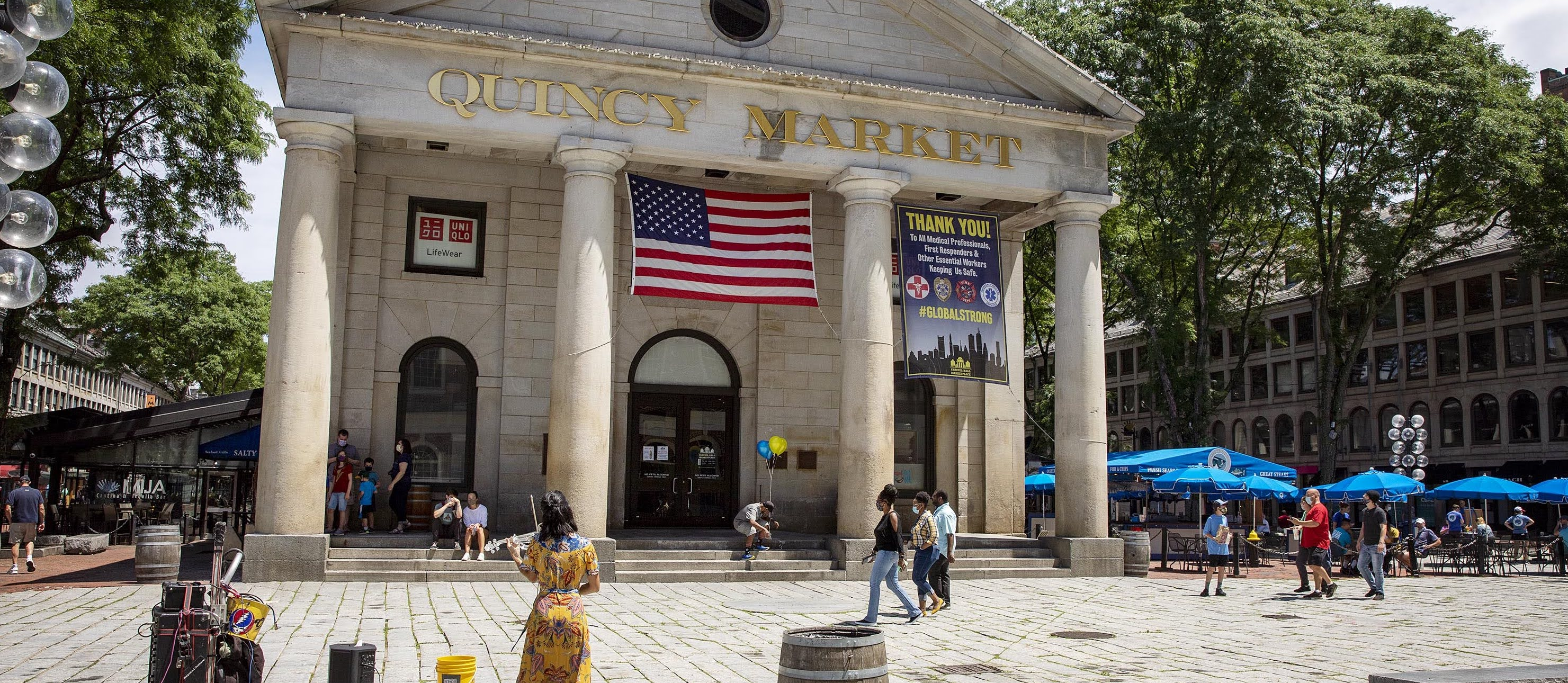 People begin to return to Quincy Market at lunchtime, as the market reopens after being closed to slow the spread of the coronavirus. (Robin Lubbock/WBUR)