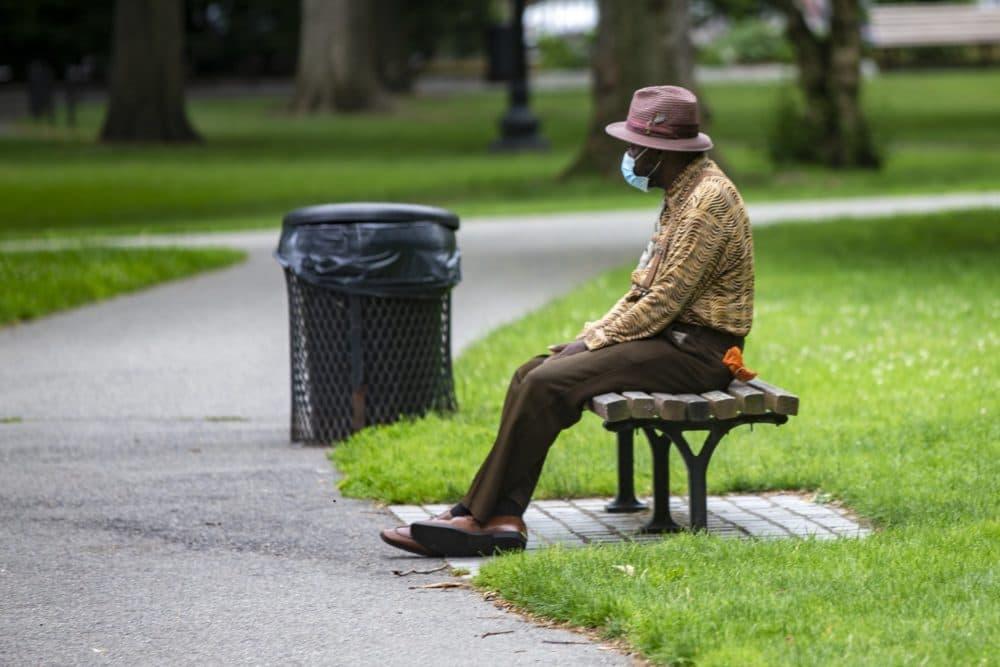 An elderly man rests on a bench in the Boston Public Garden. (Jesse Costa/WBUR)