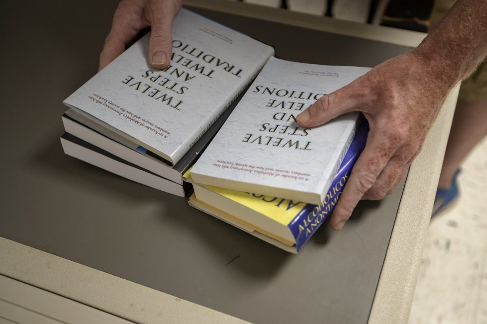 A man sets out various books on a table for Alcoholics Anonymous members to read for a meeting at St. Patrick's Church in Falmouth, Mass. (Jesse Costa/WBUR)