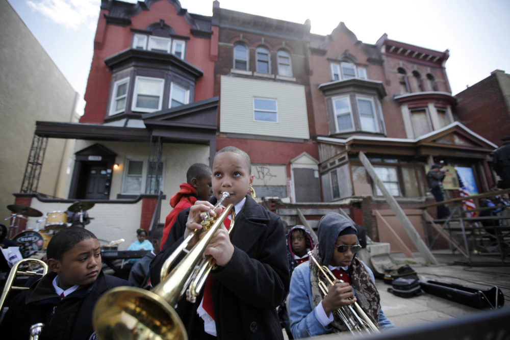 Students play music near the former home, third from left, of jazz musician John Coltrane in Philadelphia. Coltrane lived in a rowhouse in the city's Strawberry Mansion neighborhood from 1952 to 1958. (Matt Rourke/AP)