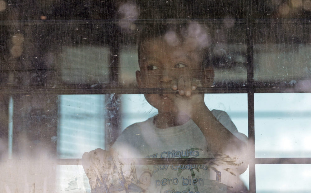 An immigrant child looks out from a U.S. Border Patrol bus leaving as protesters block the street outside the U.S. Border Patrol Central Processing Center Saturday, June 23, 2018, in McAllen, Texas. (David J. Phillip/AP)