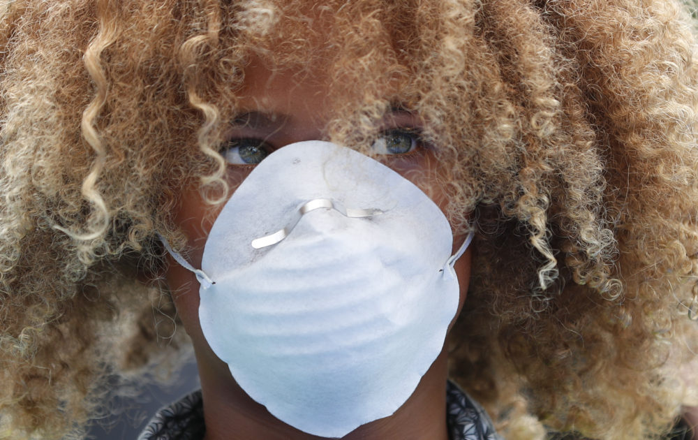 Levi Draheim, 11, wears a dust mask as he participates in a demonstration, Friday, July 12, 2019, in front of the Miami City Hall in Miami. Several youth organizations participated in the demonstration and die-in ahead of the start of Youth Climate Summit in Miami. (Wilfredo Lee/AP)