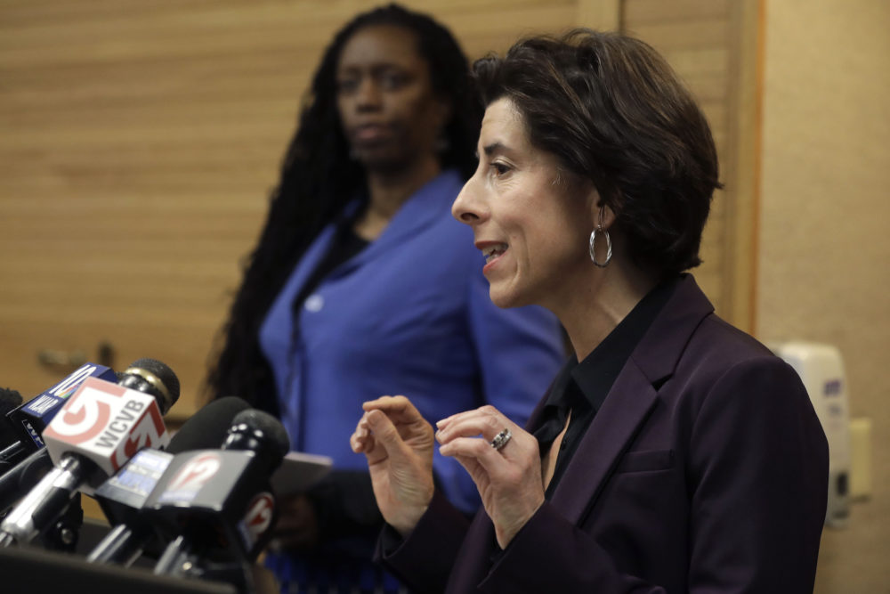 Rhode Island Gov. Gina Raimondo (right) and R.I. Director of Health Nicole Alexander-Scott (behind) face reporters during a news conference on COVID-19. (Steven Senne/AP)