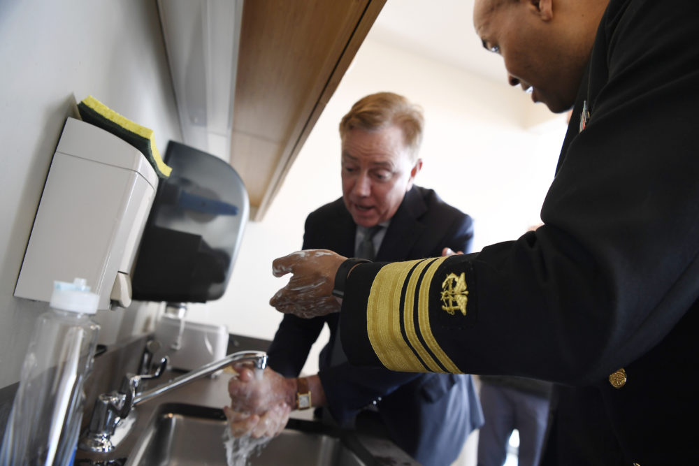 U.S. Surgeon General Vice Admiral Jerome M. Adams demonstrates how long to wash hands with Connecticut Gov. Ned Lamont. (AP Photo/Jessica Hill)