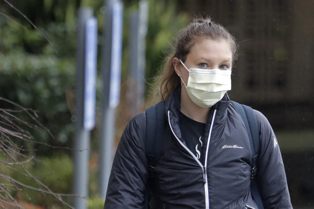 A woman wearing a mask walks away from the Life Care Center in Kirkland, Wash., near Seattle, on March 2. Health officials in Washington state said Sunday night that a second person had died from the coronavirus. (Ted S. Warren/AP)