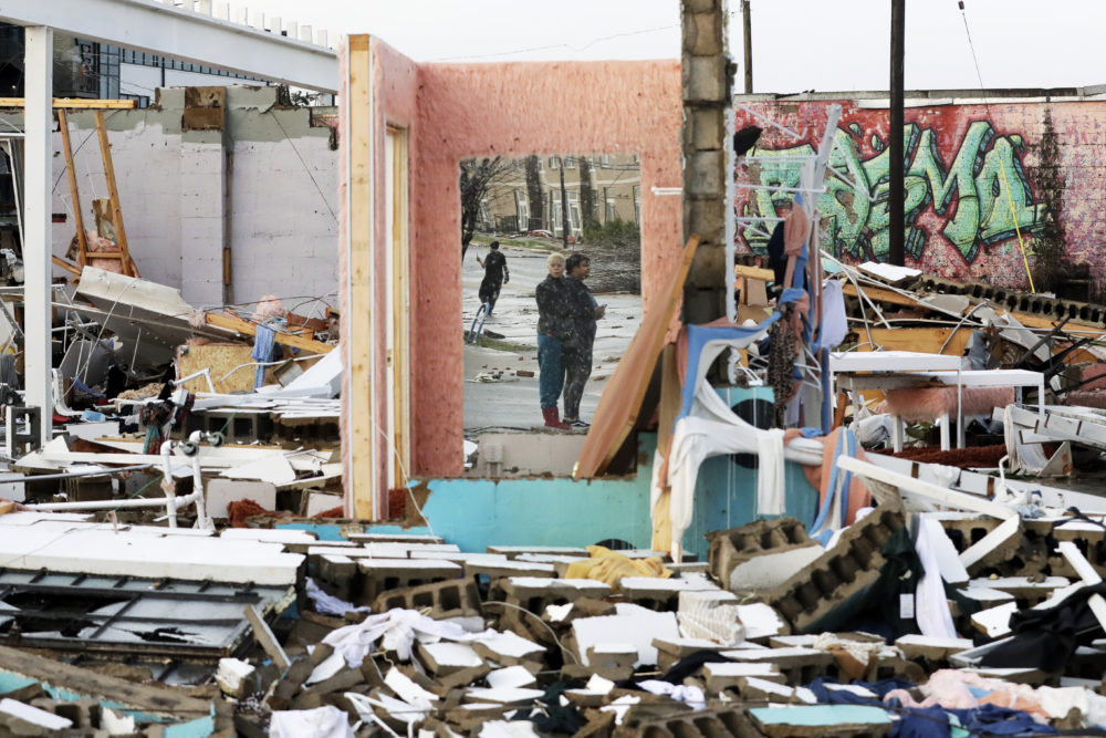 People are reflected in a mirror of a building destroyed by storms Tuesday, March 3, 2020, in Nashville, Tenn. Tornadoes ripped across Tennessee early Tuesday, shredding buildings and killing multiple people. (Mark Humphrey/AP)