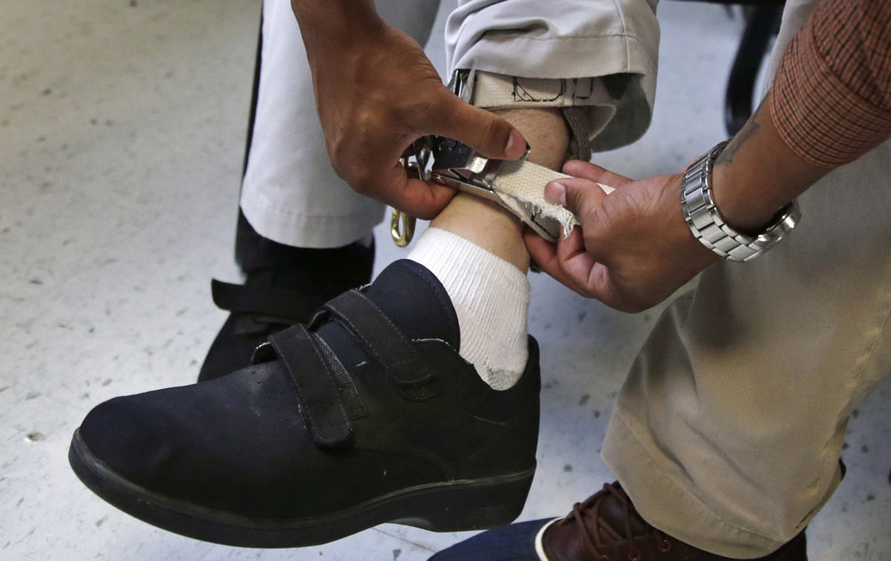 In this Aug. 2014 file photo, a therapist checks the ankle strap of an electrical shocking device on a student during an exercise program at the Judge Rotenberg Educational Center in Canton, Mass. (Charles Krupa/AP)