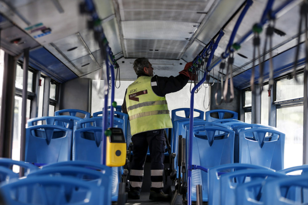 A worker sanitizes a public transport bus following the coronavirus emergency, in Rome, Friday, March 6, 2020. The Italian government has ordered all sporting events to take place without spectators and has urged the cancellation of all mass gatherings. (Cecilia Fabiano/LaPresse via AP)