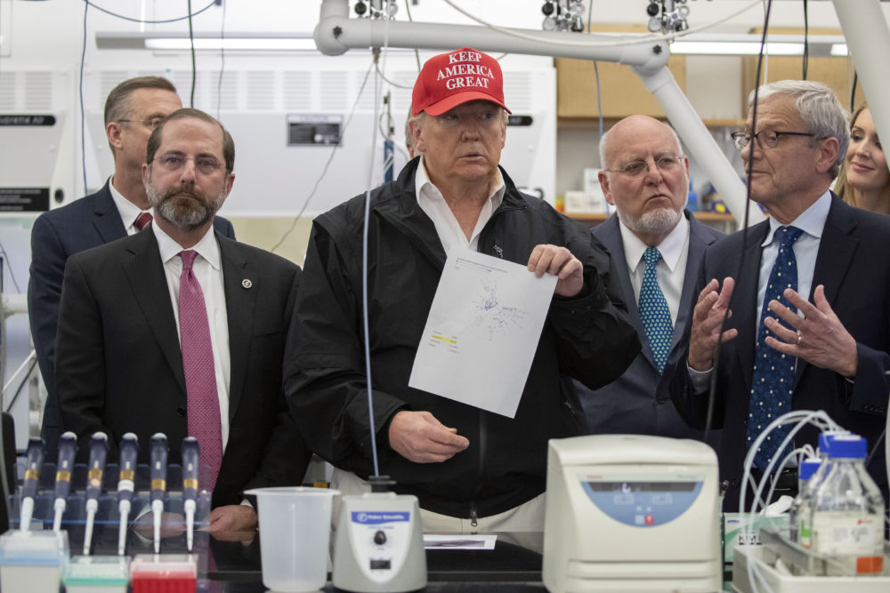 President Donald Trump holds up a picture as he listens during a meeting with Health and Human Services Secretary Alex Azar, left, Associate Director for Laboratory Science and Safety Steve Monroe, and Centers for Disease Control and Prevention Director Dr. Robert Redfield, about the coronavirus at the Centers for Disease Control and Prevention, Friday, March 6, 2020 in Atlanta. (Alex Brandon/AP)
