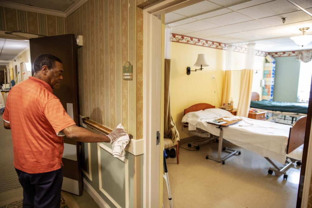 A worker at a nursing home sanitizes a handrail. (David Goldman/AP)