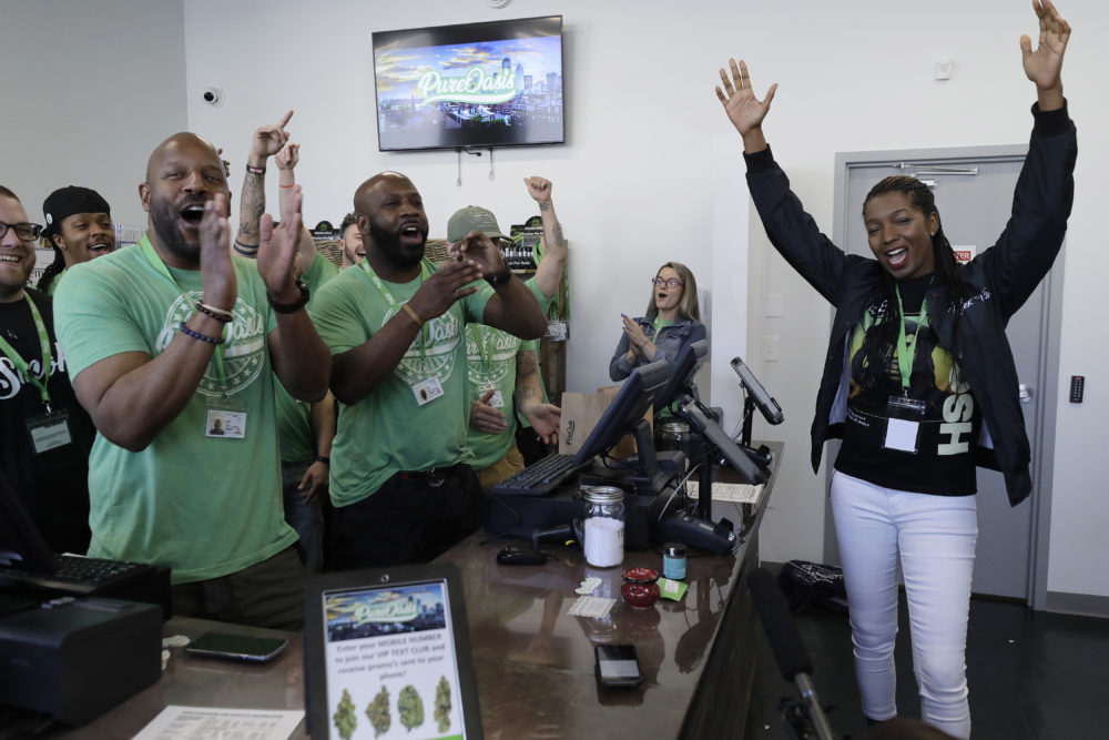 Entrepreneurs Kobie Evans, front left, and Kevin Hart, center left, celebrate the opening of Pure Oasis recreational marijuana shop with their first customer Niambe McIntosh, right, the moment the shop opened for the first time, Monday, March 9, 2020, in Boston. (Steven Senne/AP)