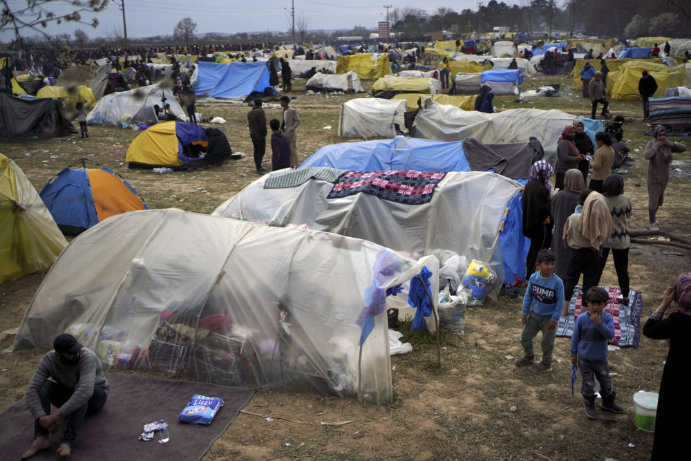 Migrants stand by tents in a camp set up near the Turkish-Greek border in Pazarkule, Edirne region, Turkey, Tuesday, March 10, 2020. (Ismail Coskun/IHA via AP)