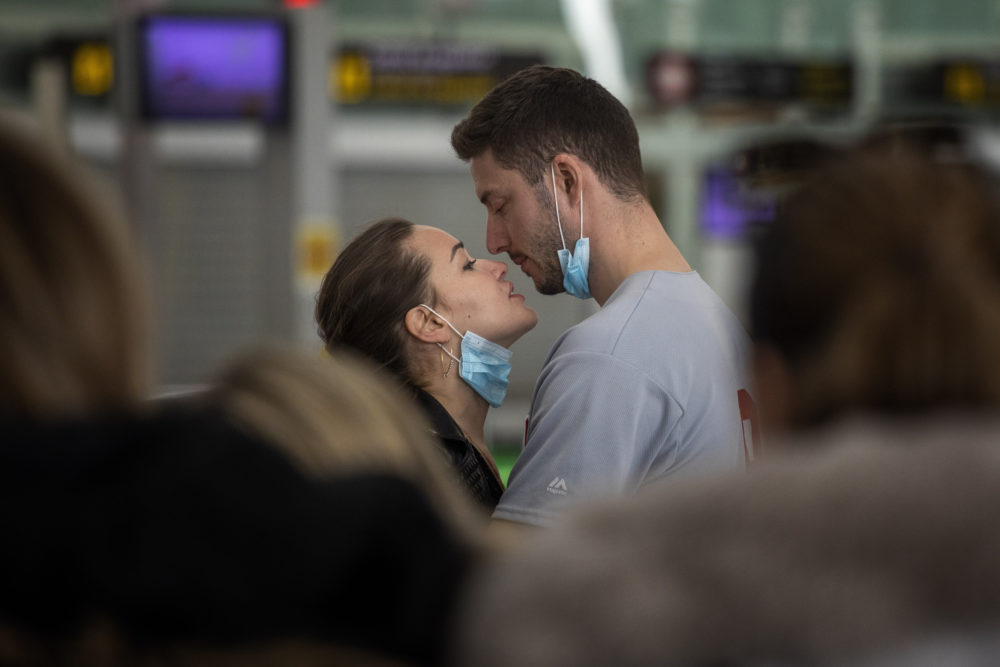 A couple kiss,  at the Barcelona airport, Spain, Thursday, March 12, 2020. (Emilio Morenatti/AP)