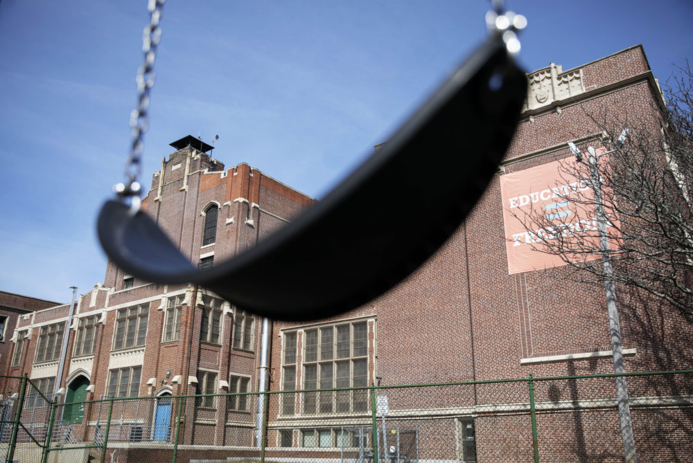 In this March 7, 2020 file photo, a swing sits empty on a playground outside Achievement First charter school in Providence, R.I. The public charter school, like a nearby Catholic school, closed after a teacher who attended the same Italy trip awaited test results for the new coronavirus. Many parents are now deciding how to talk to their children about the virus. Some said they are checking in daily, while others worry talking about it could make their kids more anxious or fearful.  (David Goldman/AP)