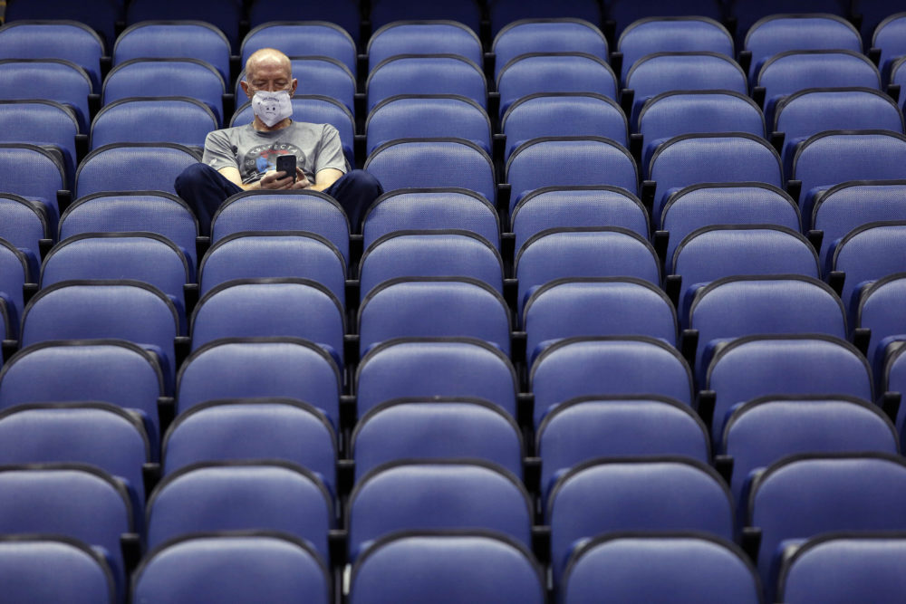 A fan sits in an empty arena after the Atlantic Coast Conference tournament was canceled. (Ben McKeown/AP)