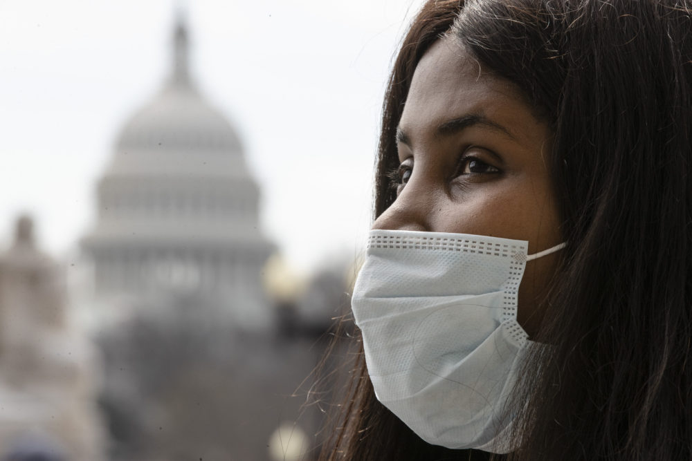 A woman wears a mask as she waits for a ride at Union Station, in view of the Capitol, Friday, March 13, 2020 in Washington. (Matt Rourke/AP)