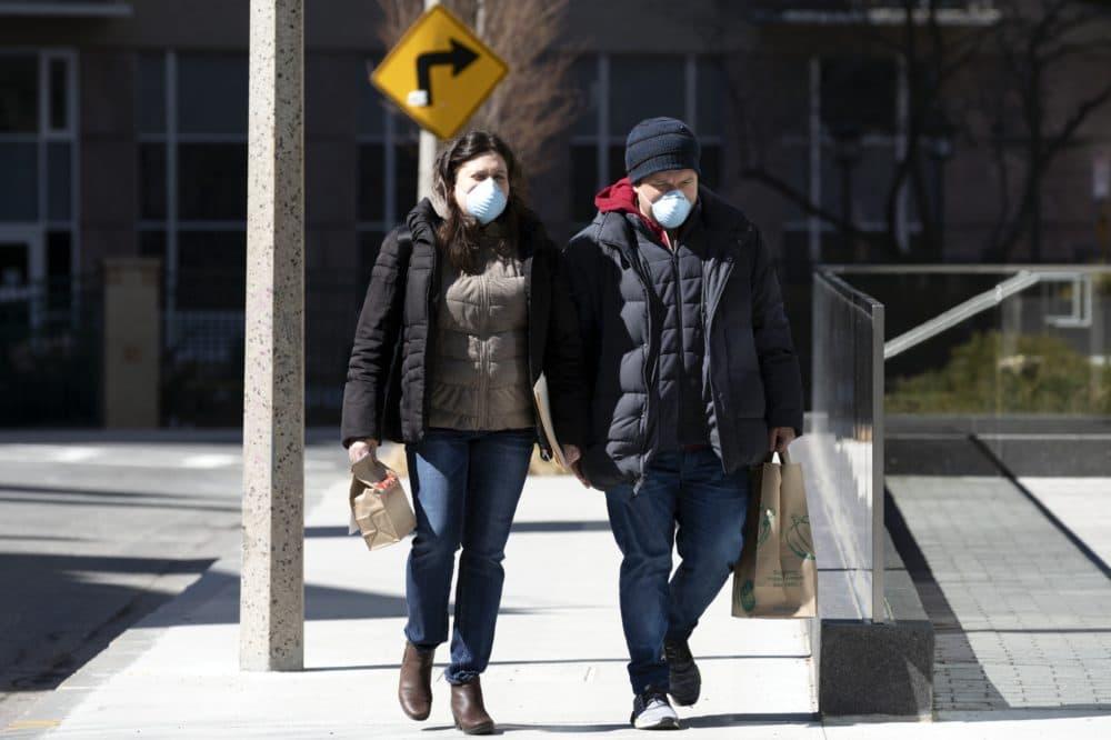 A couple wear masks while walking in Boston on Saturday. (Michael Dwyer/AP)
