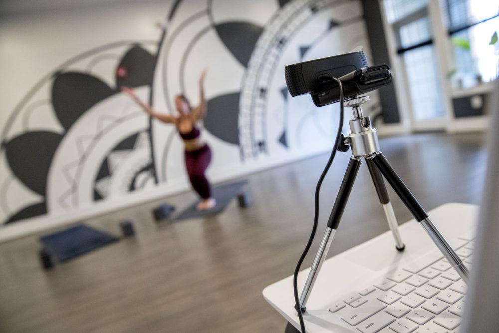 Owner Elyse DiBartolo holds a yoga class via webcam at Haus Yoga on H Street in Northeast Washington, Tuesday, March 17, 2020. DiBartolo is offering two online classes, one free class and one class just for their members, every day during the coronavirus self quarantine. (AP Photo/Andrew Harnik)